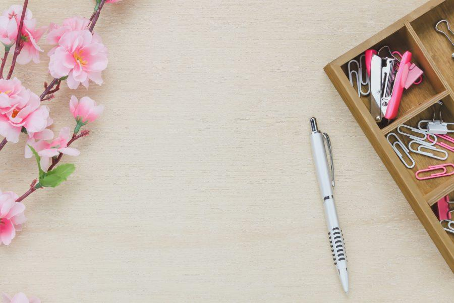 Top view business office desk background.The silver pen coffee beautiful pink flower wood shelf staple clip on wooden table backgtound with copy space.