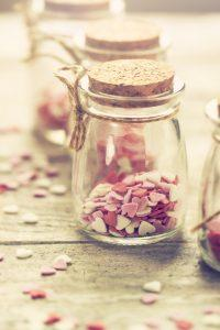 Love concept with jars on a wooden background, pastel toning.