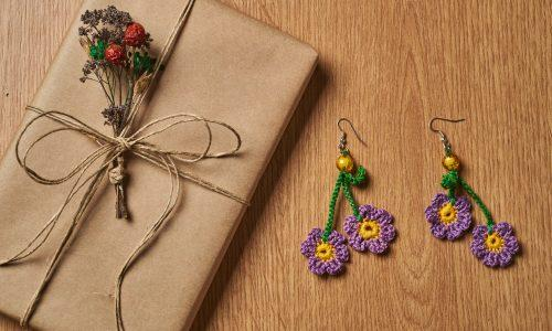 Book is wrapped in brown paper, tied with paper thread lying on the tabletop with a pair of knitted green and purple earrings lying next to it.