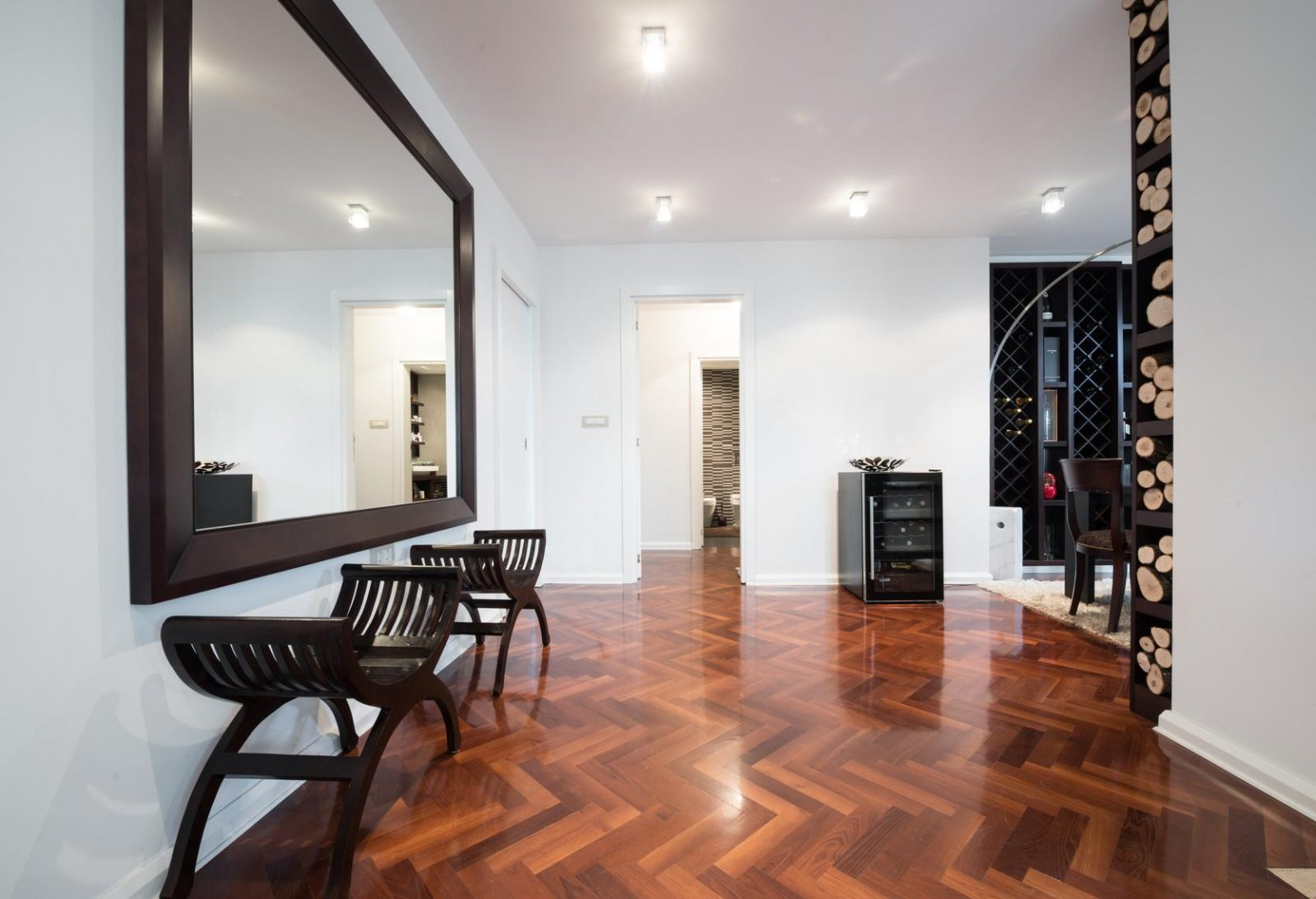 Spacious anteroom interior with large mirror and shiny brown parquet
