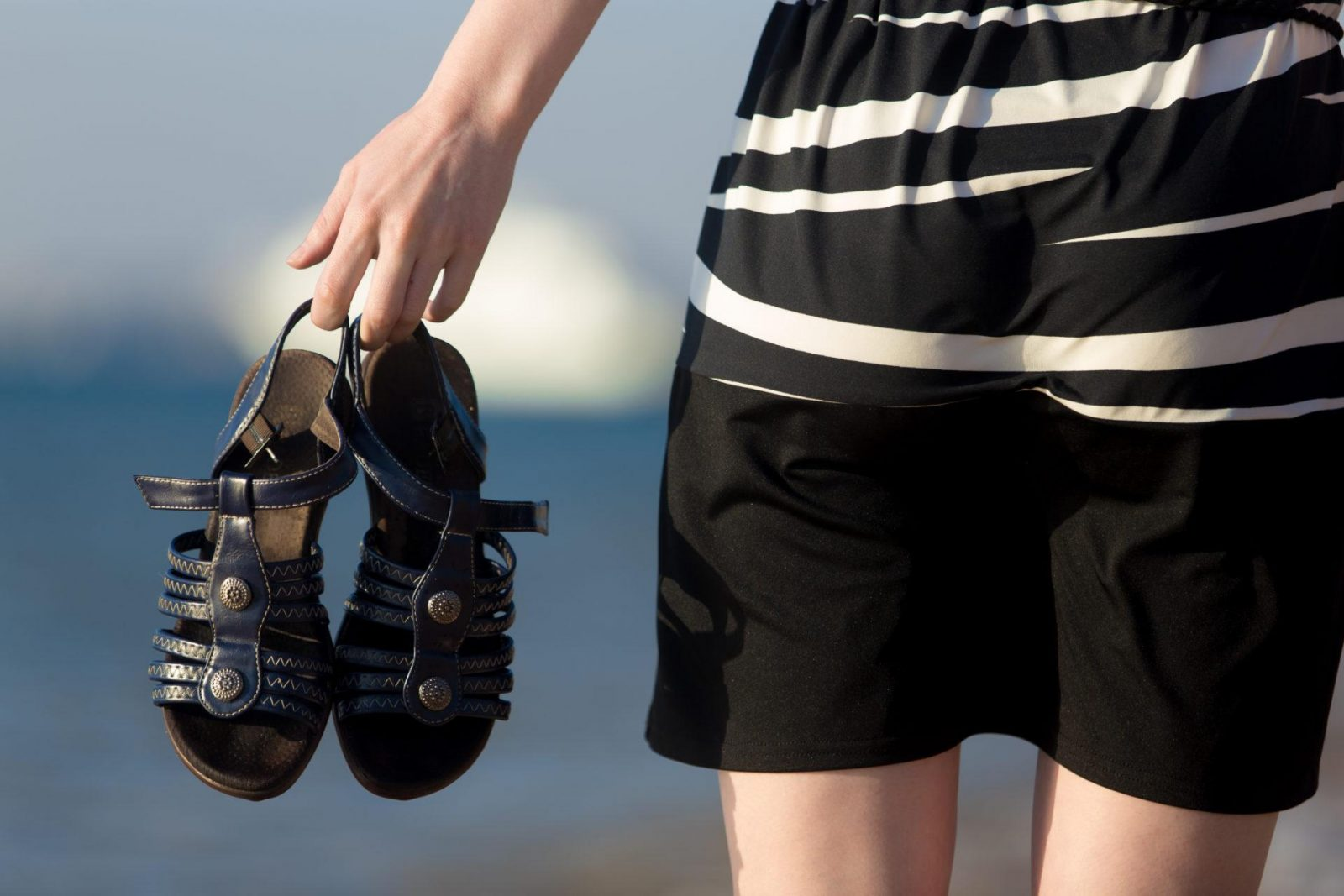 Close up of young woman hands holding blue leather sandals at sea shore, back view